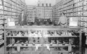 The inside of Haase's Shoe store circa 1921. Boris (left) and his wife Della (right) stand behind the shoe counter during business hours.